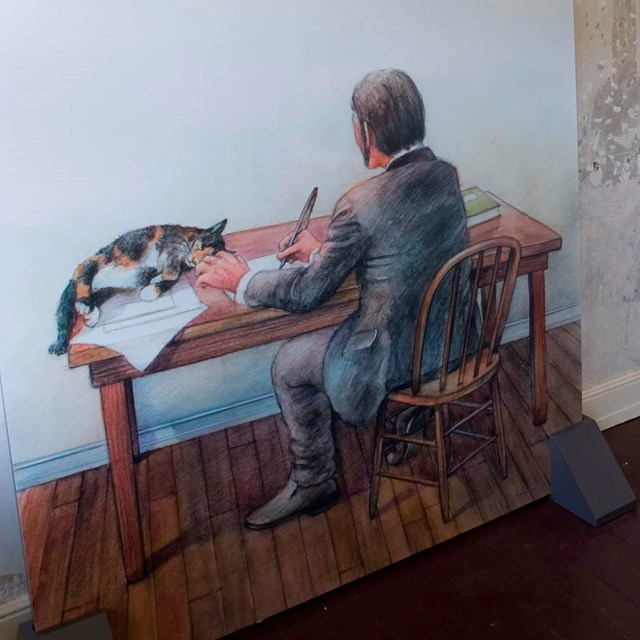 Color photo of a wall mural showing a man writing on a desk with a cat nearby.