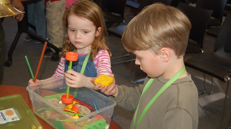 A young girl and boy hold TinkerToys in their hands as they try to make a new invention.
