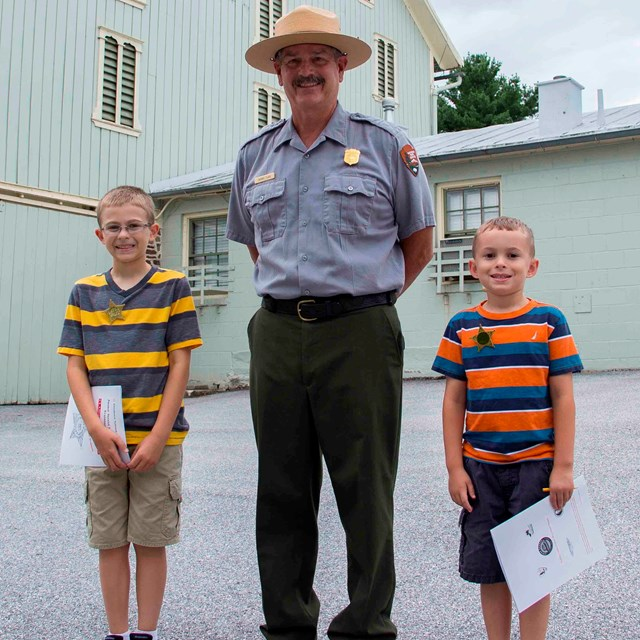 Ranger in the middle of two kids after they have completed their Junior Secret Service program.