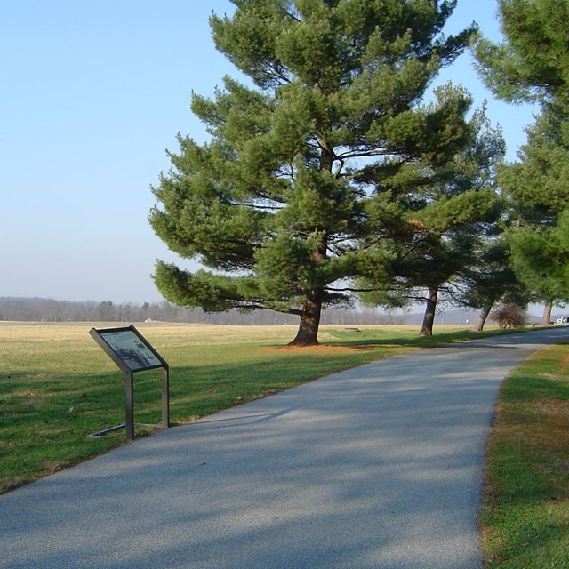 Photo of a paved trail at Eisenhower Farm overlooking an open filed with a informative sign.