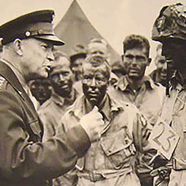 Eisenhower in uniform speaking to a solider in a black and white image.
