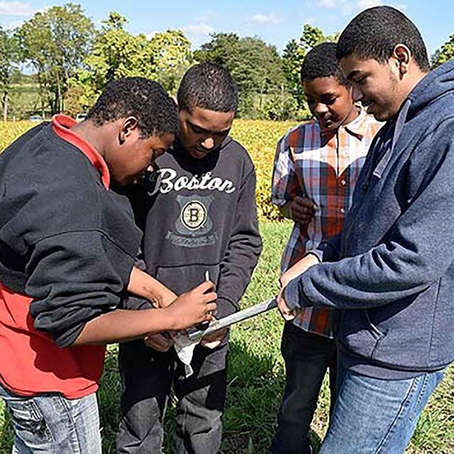 4 Students extract soil samples from the President's cropland for testing.