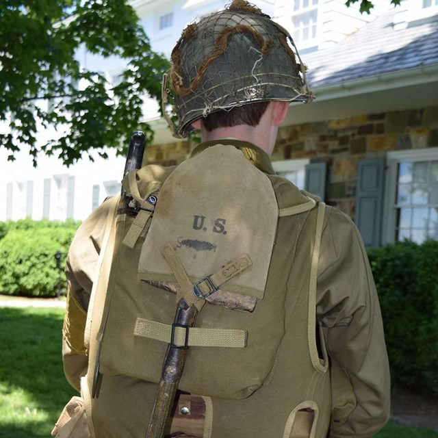 Back view of a person wearing the packs the soldiers use to use during war.