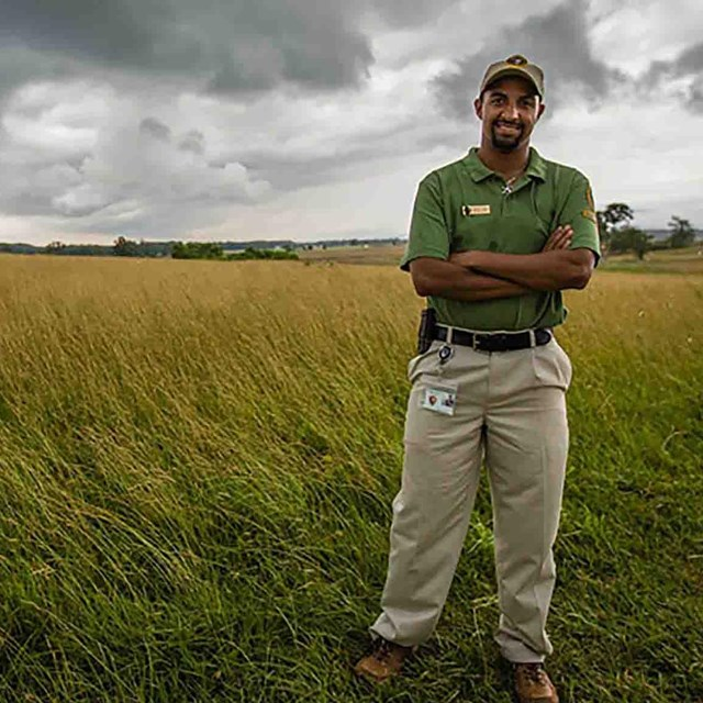 An intern poses for a picture in an open field. He's wearing a green shirt, khaki pants, & ball cap.