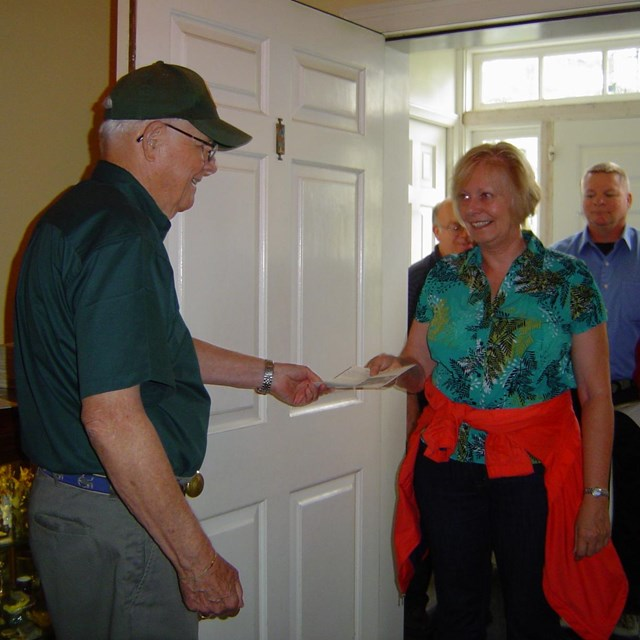 A volunteer holds the front door open for a group of visitors ready to tour the Eisenhower home.