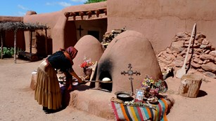 A woman uses a wooden tool to remove food from an adobe earthen oven, set against an adobe building.