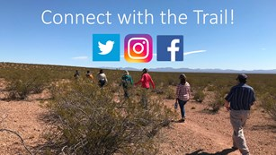 People walking down a trail in a desert setting with social media logos &