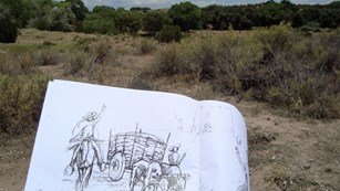 A sketchbook with a wagon train depicted is held while looking out at a forest of shrub-like trees.