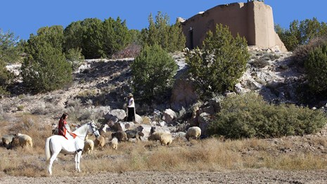 Grass in foreground, woman on white horse, sheep, sheep herder, church in background, blue sky