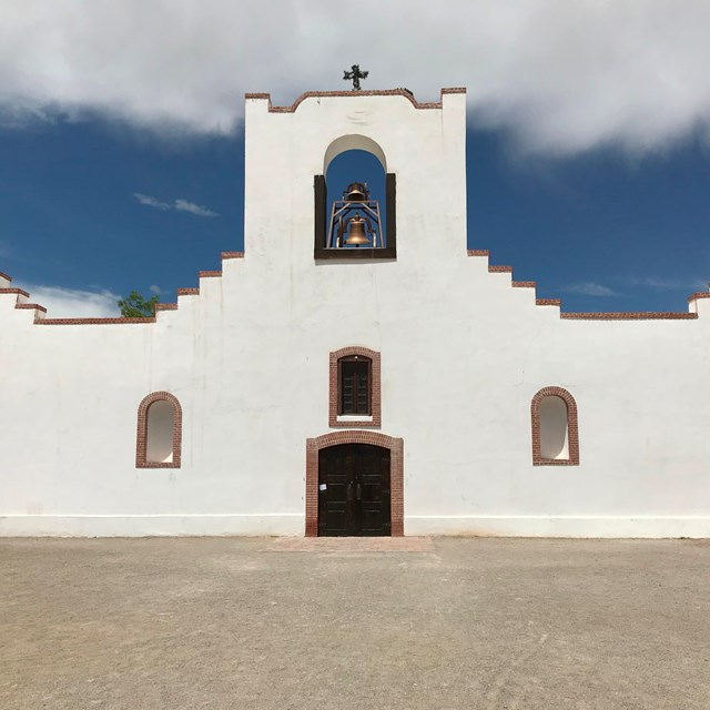 A white, spanish-style mission, under a blue sky.