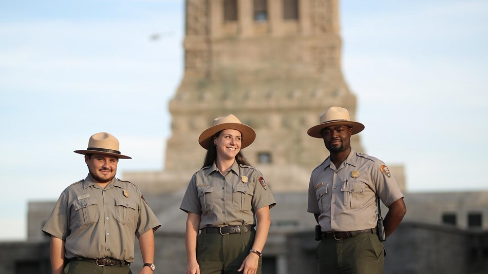 Three park rangers walking away from the backside of the Statue of Liberty