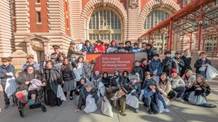 Students dressed as immigrants 100 years ago in front of the Ellis Island sign.