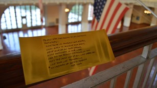 Gold Brick on Ellis Island Great Hall Railing with advice on life.