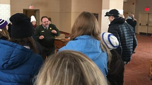 A park ranger use his hands to demonstrate his story.