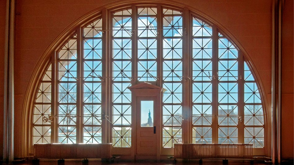 In the Great Hall of Ellis Island, looking through one of the windows towards the Statue of Liberty.