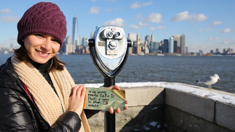 Visitor holding gold brick with message in Italian standing on Ellis Island on New York Harbor.