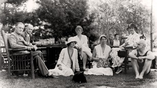 A group of people gathered together on a lawn.
