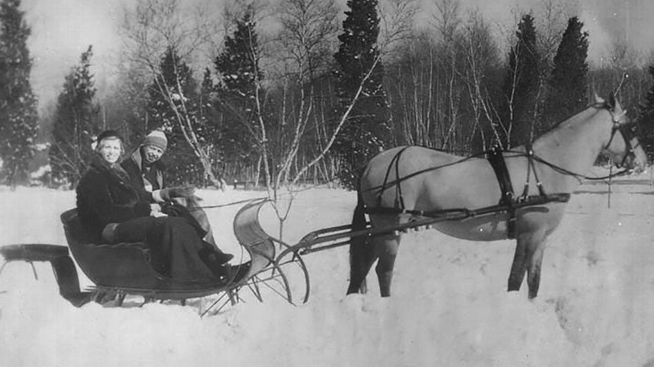 Two women in a horse drawn sleigh on a snowy landscape.
