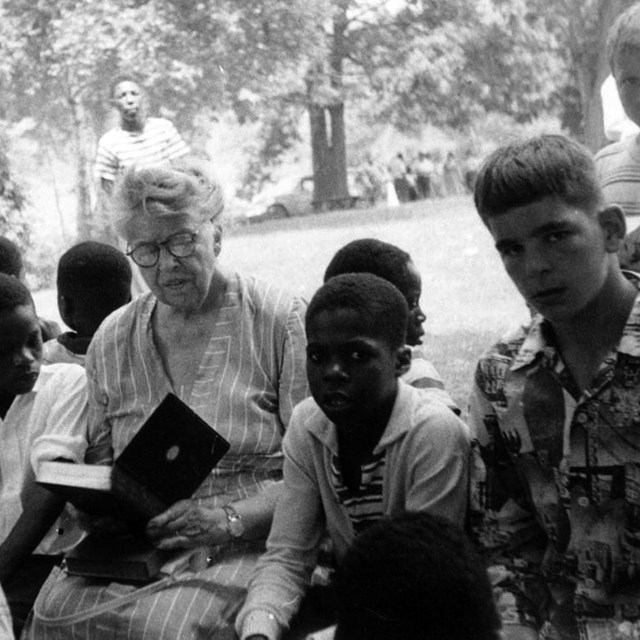 A woman reading to a group of children outdoors.