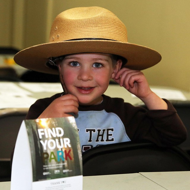 A small boy wearing a large ranger hat.