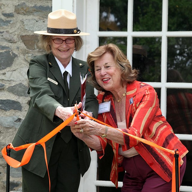 A park ranger and a woman hold a pair of scissors, cutting a ribbon.