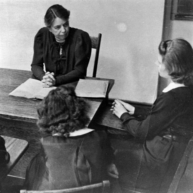 A woman at a desk conducting a class with three girls.