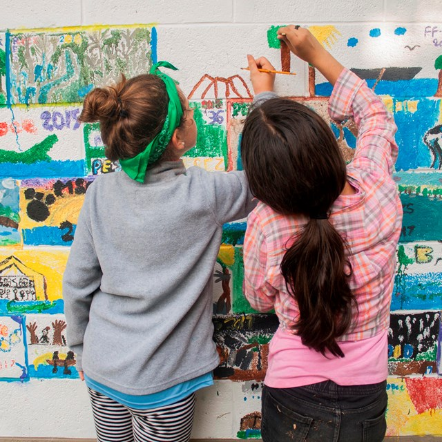 Two girls painting a colorful mural on a wall with their backs towards the camera