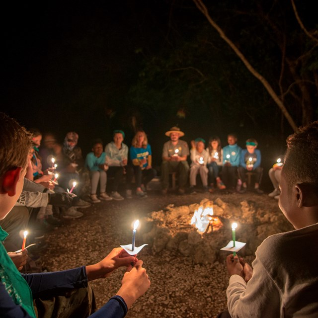 Students holding candles around a campfire.