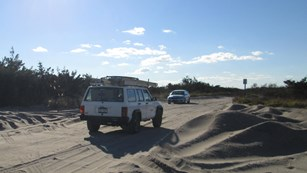 Two vehicles drive on sand road.