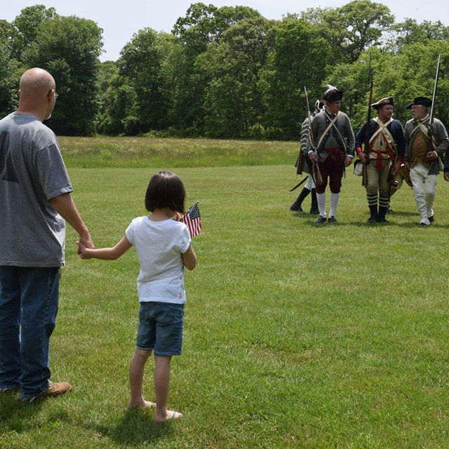 A girl holds her father's hand and watches Revolutionary War reenactors.