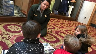A park ranger talks to children in a museum.