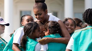 Michelle Obama hugs Girl Scouts.