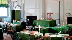 Assembly room with many tables covered with green tablecloths