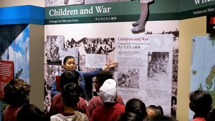 Ranger talking to school group in front of a museum exhibit about children during war