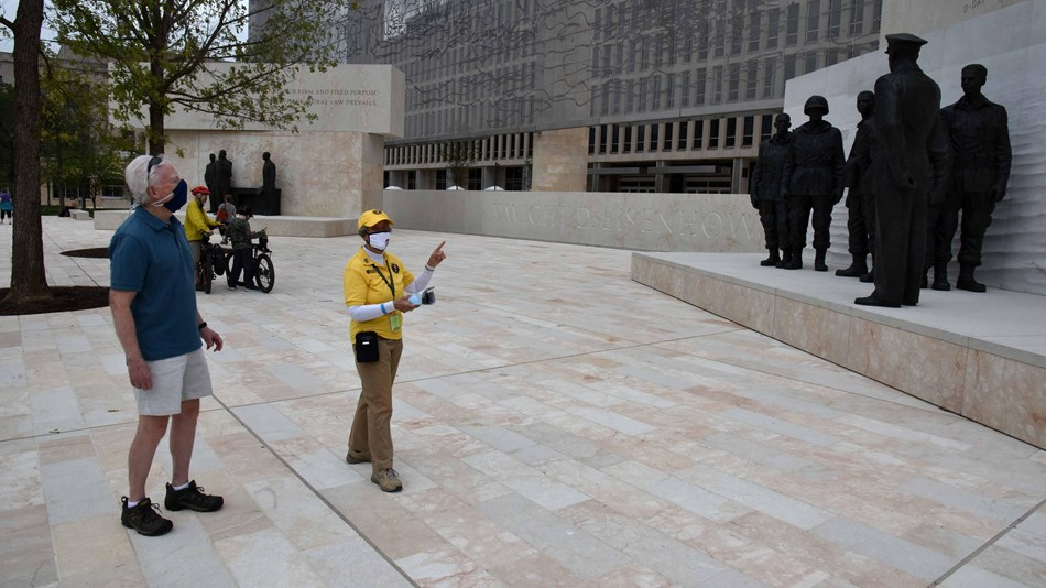 Volunteer talking to visitors on a memorial plaza