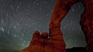 Geological arch with star trails behind it