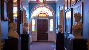 The entrance hall of the house features paintings and busts of women