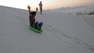 Woman sledding down a sand dune