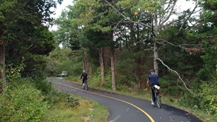 Two bicyclists on a paved trail