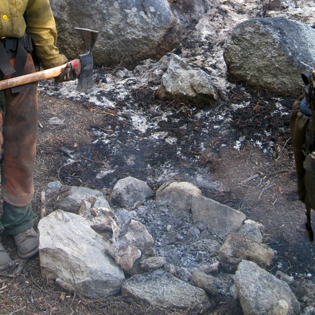 A firefighter stands next to the point of origin of an escaped campfire.