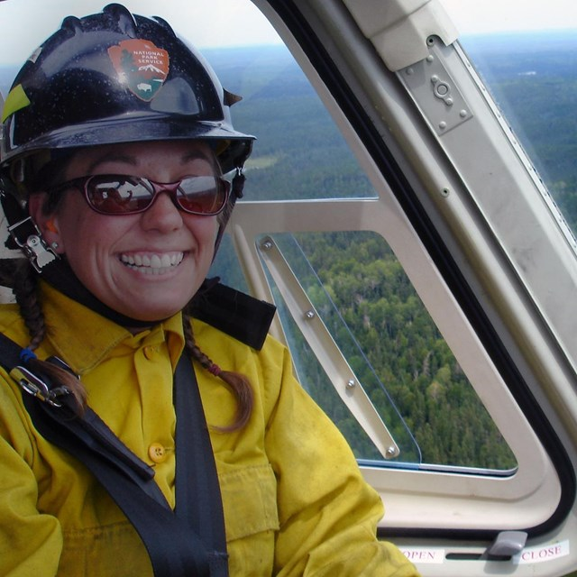 Firefighter smiling inside a helicopter flying over a national park