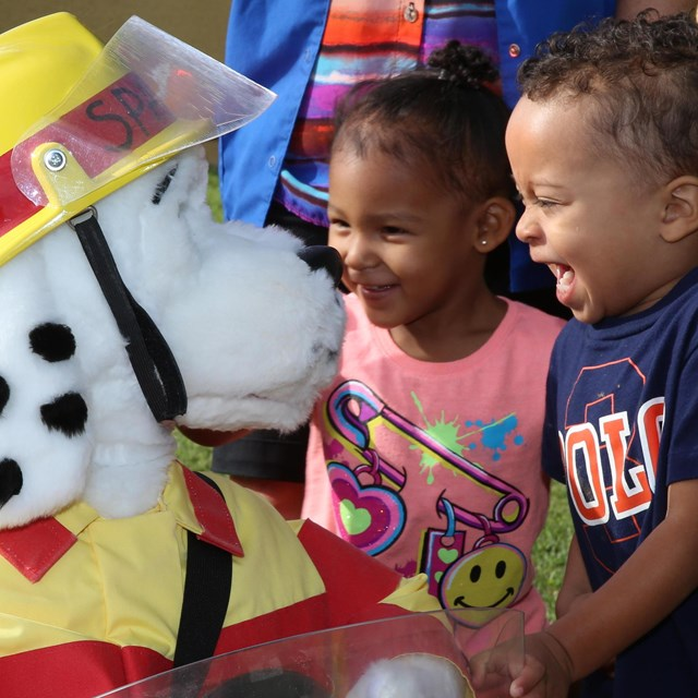 Two children laugh with Sparky the Fire Dog.