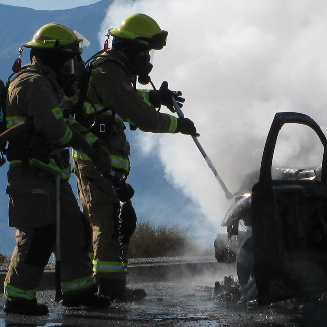 Firefighters us a hose to quell a vehicle fire.