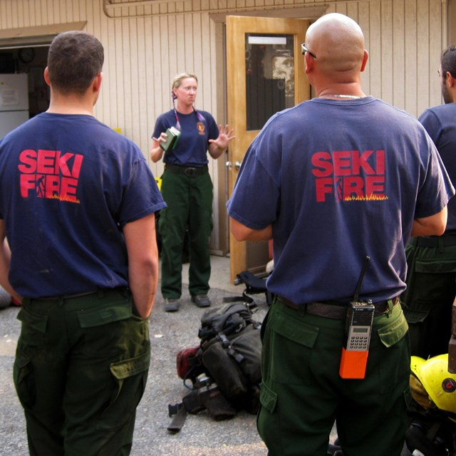 Firefighters listen to briefing before responding to a fire.