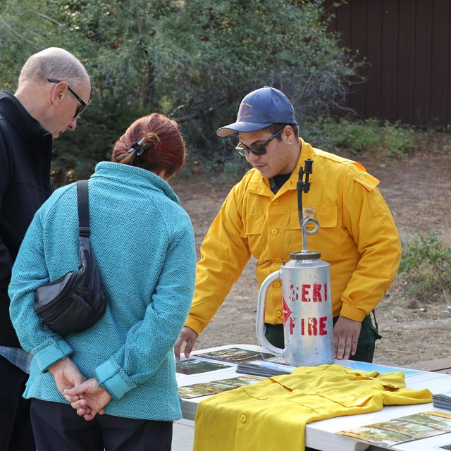 A fire information officer talks with two visitors about a prescribed burn.