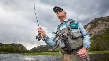 close up of man fly fishing with rod in mid air