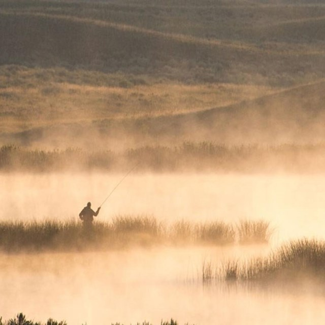 Angler fishing in lakes with steam rising.
