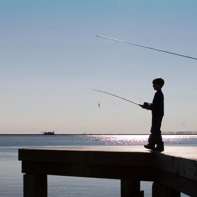 child and father fishing off of dock into ocean.