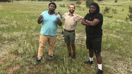 Two rappers from Oakland stand with an NPS intern in a grassy meadow at Florissant