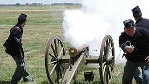 Men dressed in 19th century U.S. Army uniforms firing a cannon.